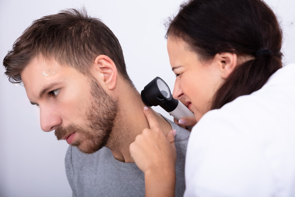 A skin doctor checking for signs of skin cancer using a dermascope , Skin cancer clinic Darwin